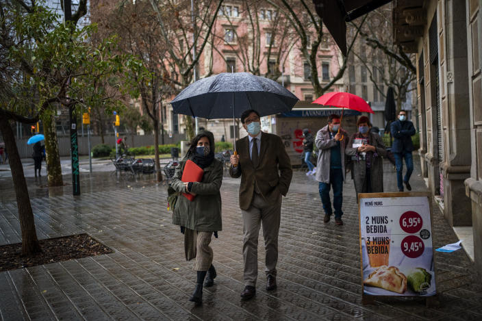 Catalan Socialist Party (PSC) candidate in the upcoming Catalan elections Salvador Illa, holds an umbrella during a walk in downtown Barcelona, Spain, Monday, Feb. 8, 2021. A former health minister of Spain hopes to become a quiet political disruptor in the country's Catalonia region when voters go to the polls next weekend. (AP Photo/Emilio Morenatti)