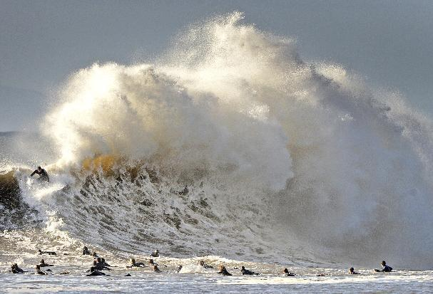 Surfers enjoy the large waves at the entrance to Santa Barbara, Calif., harbor Saturday morning, Jan. 21, 2017. A winter storm is bringing much higher than usual waves to the area. (Mike Eliason/Santa Barbara County Fire Department via AP)