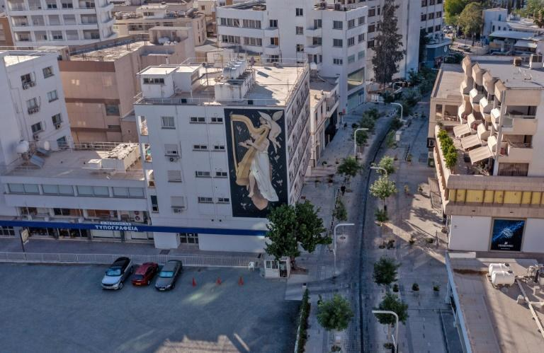 """A mural by Greek artist Fikos, who describes himself as a """"neo-muralist"""", is pictured on a building on Stasikratous Street, a major shopping area in the center of Cypriot capital Nicosia"""