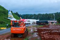 A man walks near the wreckage of an Air India Express jet at Calicut International Airport in Karipur, Kerala, on August 8, 2020. - Fierce rain and winds lashed a plane carrying 190 people before it crash-landed and tore in two at an airport in southern India, killing at least 19 people and injuring scores more, officials said on August 8. (Photo by Arunchandra BOSE / AFP) (Photo by ARUNCHANDRA BOSE/AFP via Getty Images)