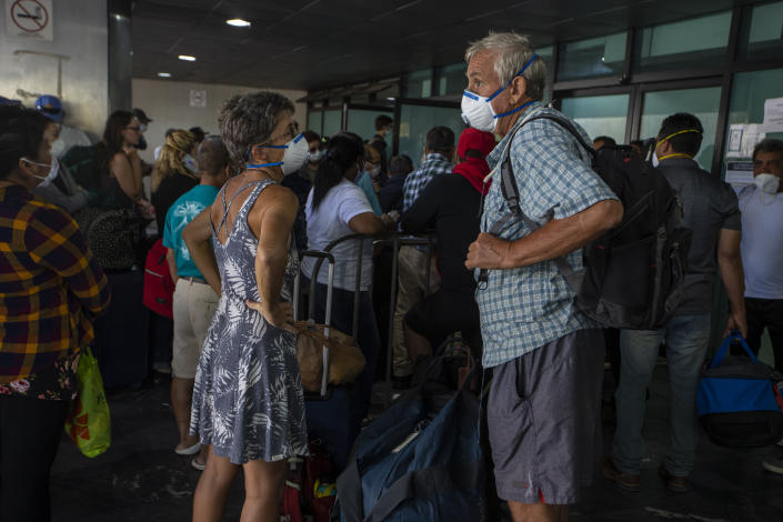 Travelers wait for a charter flight coordinated by the U.S. embassy at the La Aurora airport in Guatemala City, Tuesday, March 24, 2020. American citizens stranded abroad because of the coronavirus pandemic are seeking help in returning to the United States. (AP Photo/Moises Castillo)