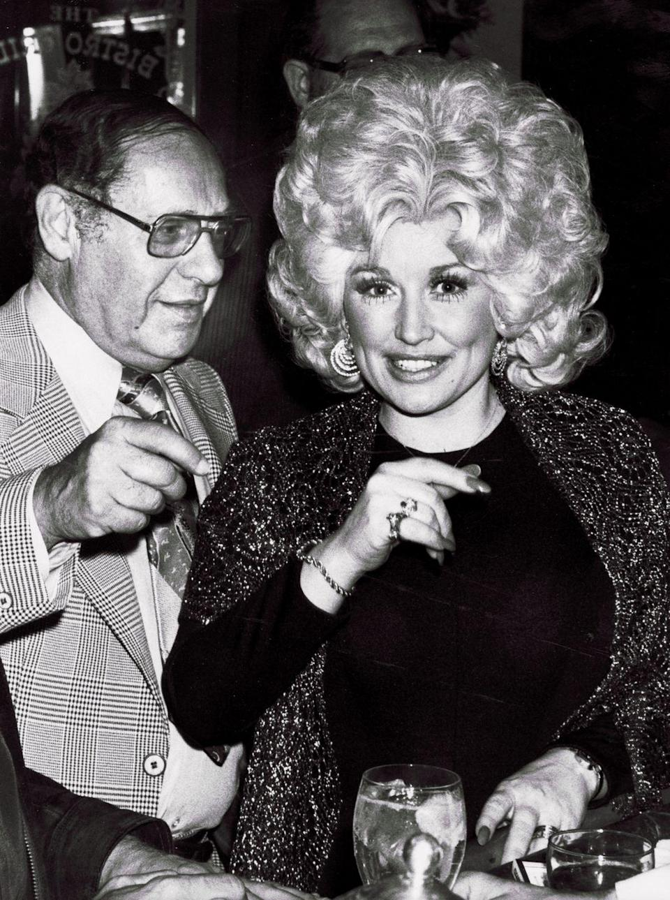 """<p>In 1977, Dolly Parton had climbed the charts with hits like """"Jolene, """"I Will Always Love You,"""" and """"Coat of Many Colors."""" She was on the cusp of making the transition to pop-country crossovers as more leaders in the industry began to realize her star potential. Here, she sparkles at an RCA party with iconic agent Lee Solters. </p>"""
