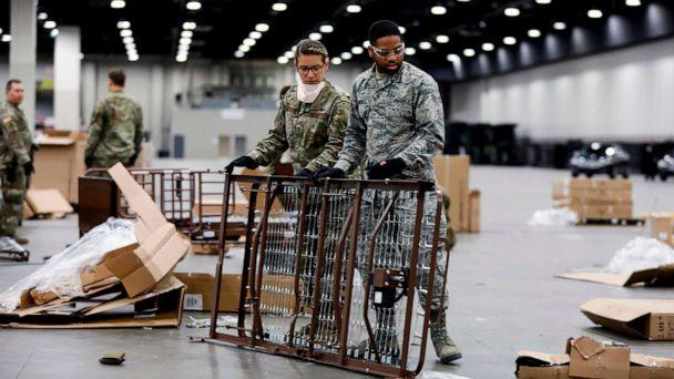 PHOTO: Members of the Michigan National Guard assemble beds at the TCF Center which is being converted by the US Army Corps of Engineers into a field hospital in Detroit, April 1, 2020. (Jeff Kowalsky/AFP/Getty Images)