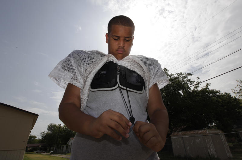 Twelve-year-old Elijah Earnheart dons his practice pads for photos outside his home in Mesquite, Texas, Thursday, Aug. 16, 2012. The 6-foot, 300-pound 12-year-old has been ruled ineligible to play Pee Wee football in the Dallas area. Despite being a young seventh-grader, officials say is more than twice the maximum allowable Pee Wee weight of 135 pounds. (AP Photo/LM Otero)