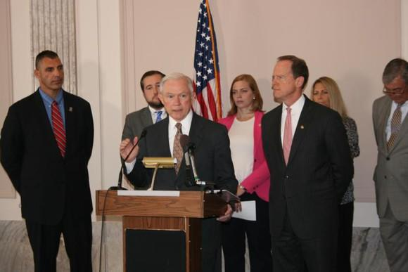 Jeff Sessions addressing an audience from behind a podium and surrounded by a group of colleagues.
