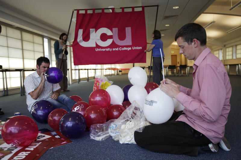Members of Britain's University and College Union (UCU) pose for members of the media as they prepare for their union strike and march scheduled for Thursday as they prepare in their headquarters in north London, Wednesday, June 2, 2011.  Thousands of British schools will close and travelers will face long lines at airport immigration this week when three quarters of a million workers go on strike - the first blast in what unions hope will be a summer of discontent against the cost-cutting government's austerity plans. The first test comes when 750,000 public-sector workers - from teachers to driving examiners to customs officials - walk out for the day, part of a growing wave of opposition to the Conservative-led government's deficit-cutting regime of tax hikes, benefit curbs and spending cuts.(AP Photo/Lefteris Pitarakis)