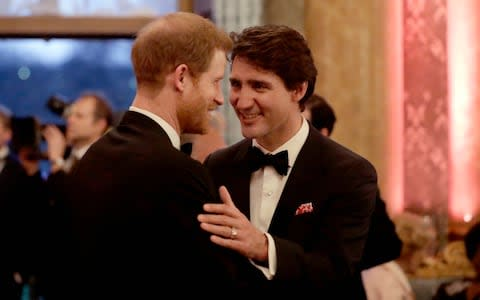 Britain's Prince Harryspeaks with Canadian Prime Minister Justin Trudeau during a reception in April 2018 - Credit: Matt Dunham/AP