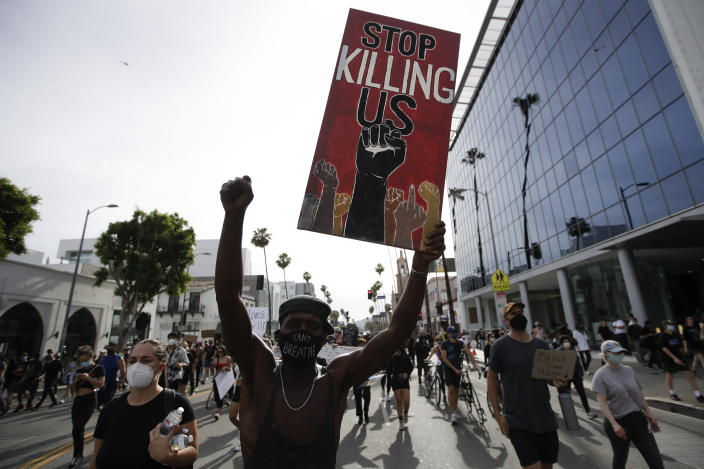 FILE - In this June 1, 2020, file photo, a protester carries a sign in the Hollywood area of Los Angeles during demonstrations over the death of George Floyd. Black people are facing a combination of stressors hitting simultaneously: isolation during the pandemic, a shortage of mental health care providers and racial trauma inflicted by repeated police killings of Black people. Black people suffer disproportionately from COVID-19 and have seen soaring rates in youth suicide attempts. (AP Photo/Marcio Jose Sanchez, File)