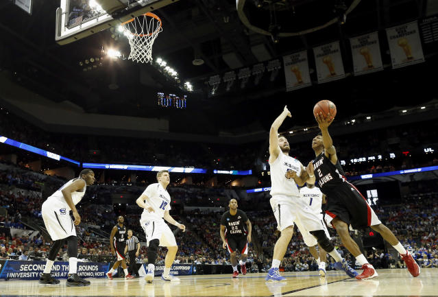 Louisiana Lafayette's Elfrid Payton (2) goes up for a shot as Creighton's Ethan Wragge (34) defends during the second half of a second-round game in the NCAA college basketball tournament Friday, March 21, 2014, in San Antonio. Creighton won 76-66. (AP Photo/David J. Phillip)