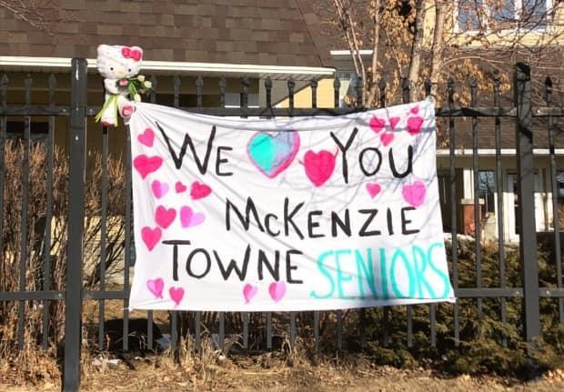 This sign was posted on the fence outside the McKenzie Towne Continuing Care Centre in southeast Calgary last spring as a COVID-19 outbreak swept through the facility.  (Jennifer Wiebe - image credit)