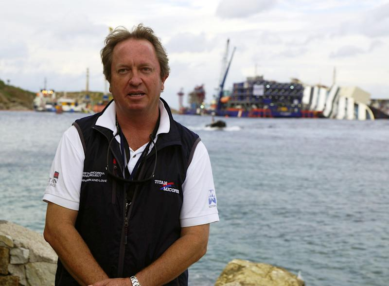 Salvage expert Nick Sloane poses after a news conference as the Costa Concordia is seen in background, on the Tuscan Island of Giglio, Italy, Sunday, Sept. 15, 2013. Authorities have given the final go-ahead for a daring attempt Monday to pull upright the crippled Costa Concordia cruise liner from its side in the waters off Tuscany, a make-or-break engineering feat that has never before been tried in such conditions. Salvage master Nick Sloane seemed optimistic in the final hours before the operation began, saying Sunday that testing of the machinery in recent days had actually lifted the 300-meter (985-foot) ship up about 10 centimeters (2.5 inches), or 0.15 degrees. (AP Photo/Alessandro La Rocca, Lapresse)