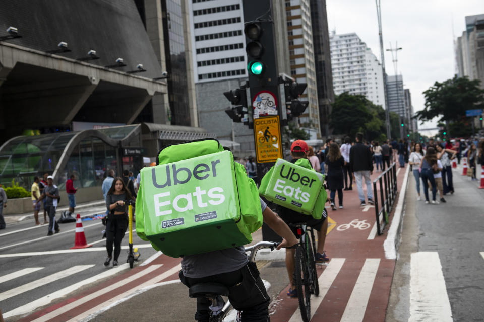 São Paulo, Brazil - April 14, 2019: Two young men working for Uber Eats cycle down Avenida Paulista, a major thoroughfare in São Paulo, delivering food carried in backpacks.