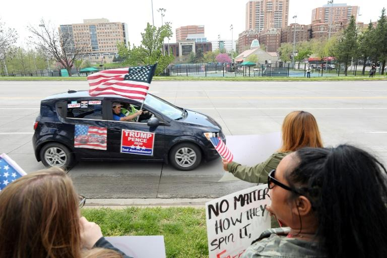 A supporter of President Donald Trump in Kansas City, Missouri waves an American flag during a protest against restrictions imposed on businesses to fight the COVID-19 pandemic