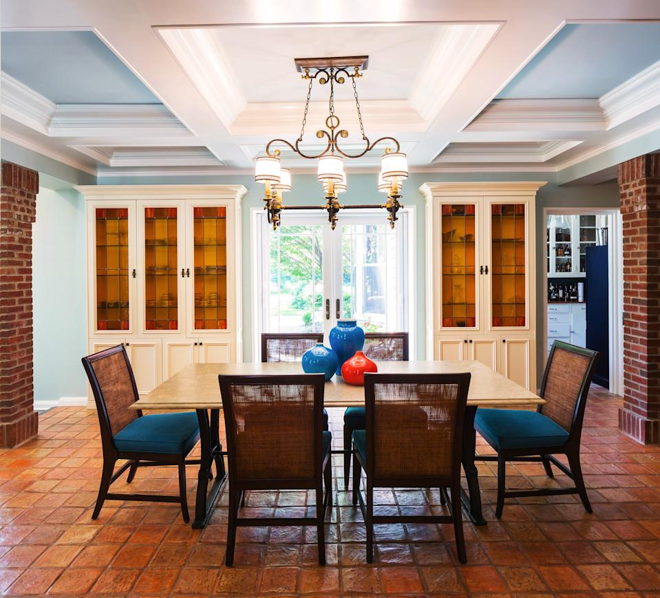 """<div class=""""caption""""> In the dining room of a large home in Sands Point, New York, designed by Courtney McLeod of Right Meets Left Interior Design, the clients wanted to keep the terra-cotta floors, the built-in cabinets, and the overhead light fixture that were all original to the home. To modernize the space, McLeod painted the ceiling coffers a blend of <a href=""""https://www.benjaminmoore.com/en-us"""" rel=""""nofollow noopener"""" target=""""_blank"""" data-ylk=""""slk:Benjamin Moore"""" class=""""link rapid-noclick-resp"""">Benjamin Moore</a>'s Simply White and Palladian Blue and added a custom-made table, as well as chairs from <a href=""""https://www.palecek.com/"""" rel=""""nofollow noopener"""" target=""""_blank"""" data-ylk=""""slk:Palecek"""" class=""""link rapid-noclick-resp"""">Palecek</a>. </div>"""