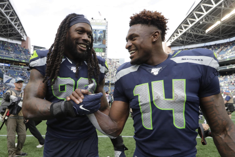 Seattle Seahawks defensive end Jadeveon Clowney, left, talks with teammate DK Metcalf, right, after they defeated the Cincinnati Bengals in an NFL football game Sunday, Sept. 8, 2019, in Seattle. (AP Photo/John Froschauer)