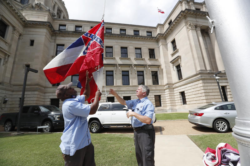 Mississippi Department of Finance and Administration employees Willie Townsend, left, and Joe Brown, raise a couple of Mississippi state flags over the Capitol grounds in Jackson, Miss., Tuesday, June 30, 2020. The two men raised and lowered about 100 flags, provided by the Secretary of State's office, for people or organizations that purchased a state flag that flew over the grounds. Gov. Tate Reeves will sign a bill Tuesday evening retiring the last state flag with the Confederate battle emblem during a ceremony at the Governor's Mansion. Upon the governor signing the bill, the flag will lose its official status. (AP Photo/Rogelio V. Solis)