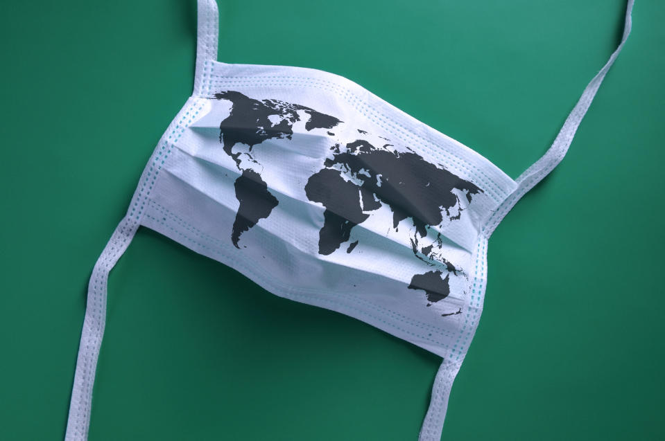 White face mask with a map of the world is lying on a blue background.