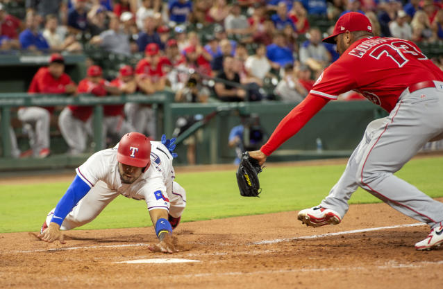Texas Rangers' Robinson Chirinos scores ahead of the tag of Los Angeles Angels relief pitcher Osmer Morales (73) on a wild pitch by Morales during the eighth inning of a baseball game Thursday, Aug. 16, 2018, in Arlington, Texas. Texas won 8-6. (AP Photo/Jeffrey McWhorter)
