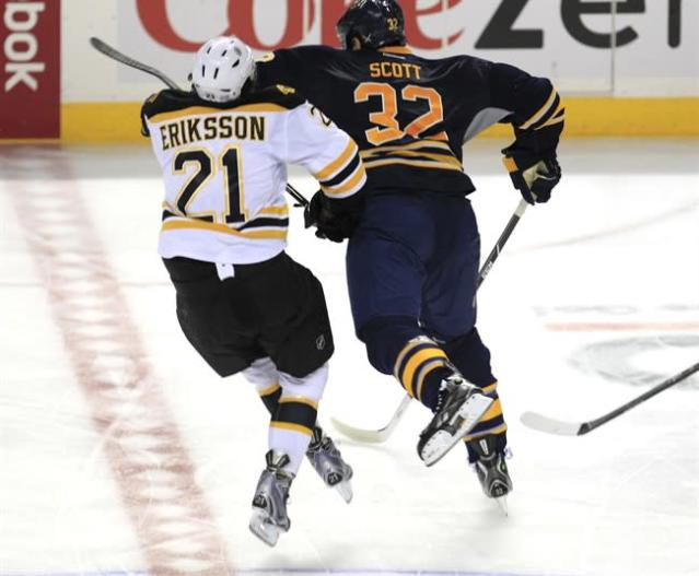 Buffalo Sabres John Scott (32) checks Boston Bruins Loui Eriksson (21) during third period action at the First Niagara Center in Buffalo on Wednesday, Oct. 23, 2013. Scott has been suspended indefinitely by the NHL pending a disciplinary hearing for a blindside hit to the head that levelled Eriksson. THE CANADIAN PRESS/AP/,Harry Scull Jr./Buffalo News