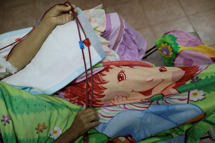Maria Esis, 52, a patient with kidney disease, rests during a dialysis session at a dialysis center after a blackout in Maracaibo, Venezuela. (Photo: Ueslei Marcelino/Reuters)