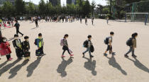 Students wearing face masks as a precaution against the new coronavirus, walk to their classrooms while maintaining social distancing after they attend the entrance ceremony at Chungwoon elementary school in Seoul, South Korea, Wednesday, May 27, 2020. More than 2 million high school juniors, middle school seniors, first- and second-grade elementary school children and kindergartners were expected to return to school on Wednesday. (Lee Jin-wook/Yonhap via AP)
