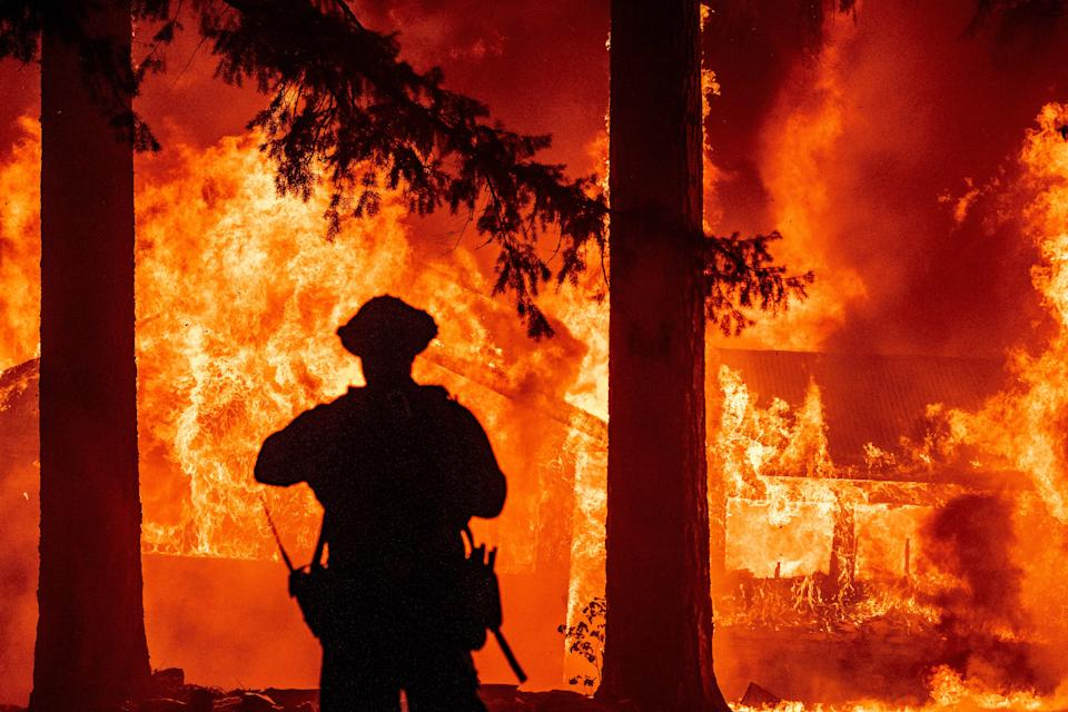 Firefighters try to get control of the scene as the Dixie fire burns dozens of homes in the Indian Falls neighborhood of unincorporated Plumas County, California on July 24, 2021. - The Dixie fire, which started only a few miles from the origin of the deadly Camp fire, has churned through more than 185,000 acres and continues to burn towards rural communities. (Photo by JOSH EDELSON / AFP) (Photo by JOSH EDELSON/AFP via Getty Images)