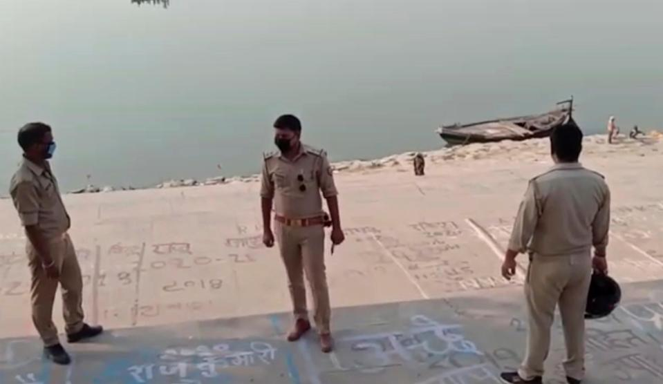 <p>Frame grab from video provided by KK Productions shows police officials stand at the banks of the river where several bodies were found in Ghazipur district in Uttar Pradesh on 11 May, 2021.</p> (AP)