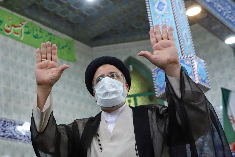 Presidential candidate Ebrahim Raisi gestures after casting his vote (VIA REUTERS)