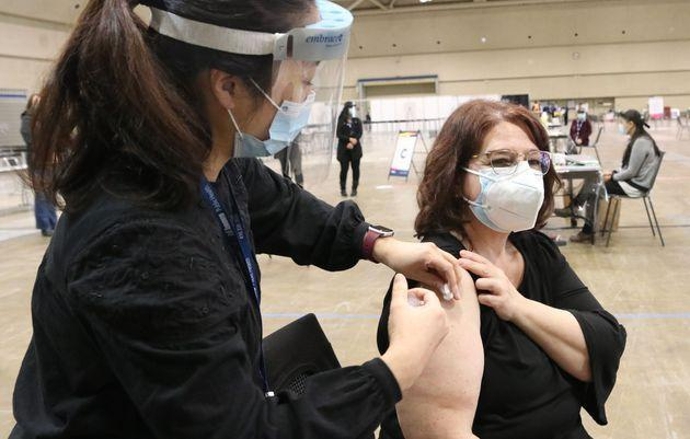 A woman receives a vaccine for COVID-19 at the Metro Toronto Convention Centre in Toronto on Jan. 18, 2021.