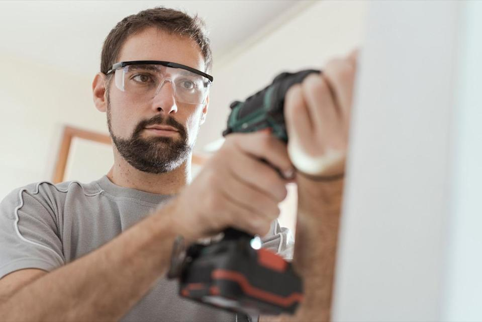 repairman with protective goggles, he is using a drill and doing a home renovation