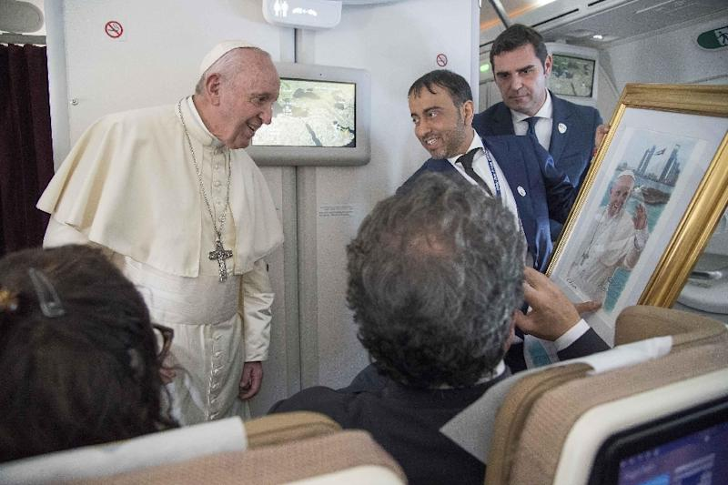 """Pope Francis, shown here accepting a gift from an Arab journalist aboard the papal plane, said the problem of sexual abuse by priests could be found """"anywhere"""""""
