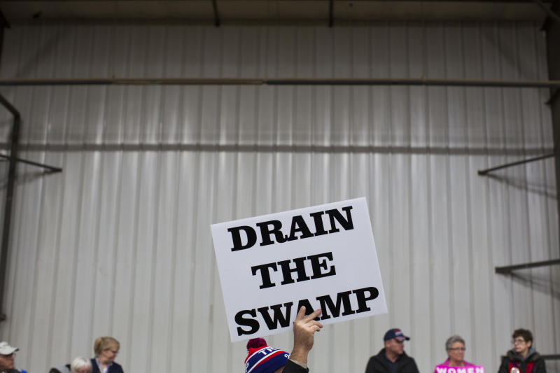 "FILE - In this Oct. 27, 2016 file photo, supporters of then-Republican presidential candidate Donald Trump hold signs during a campaign rally in Springfield, Ohio. The Trump administration insists that ""drain the swamp"" is more than a throwaway catchphrase, yet in the last three months, the White House has become less transparent, hired scores of special interest players, raised money from lobbyists and taken no concrete steps to address campaign finance. (AP Photo/ Evan Vucci, file)"