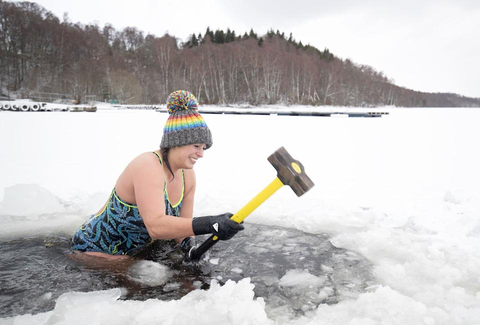 Alice Goodridge uses a sledgehammer to create a channel in the ice in Loch Insh, in the Cairngorms National Park (Jane Barlow/PA)