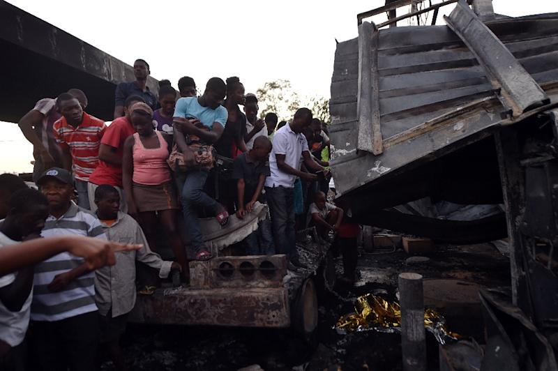 Haitians look at the damage after an explosion at a gas station in Hinche, 110 kilometers (65 miles) from Port-au-Prince, on March 17, 2016, in which at least seven people were killed
