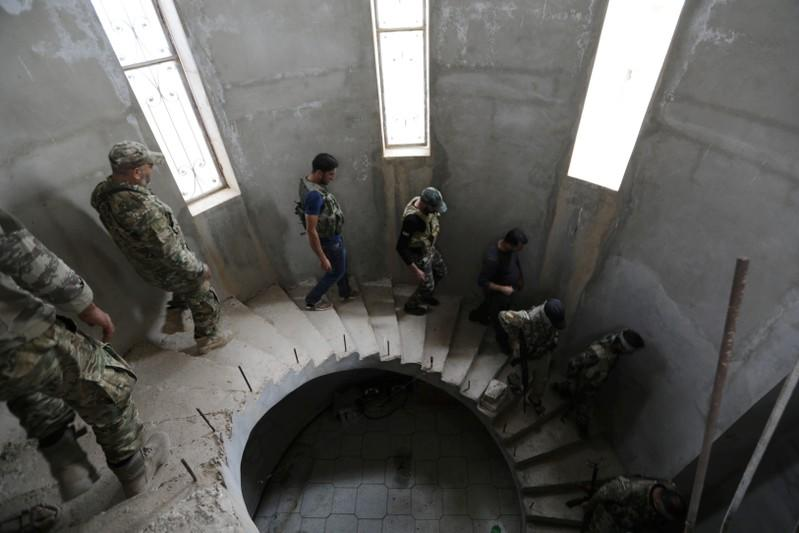 Turkey-backed Syrian rebel fighters walk inside a building they use to shelter near the border town of Tal Abyad