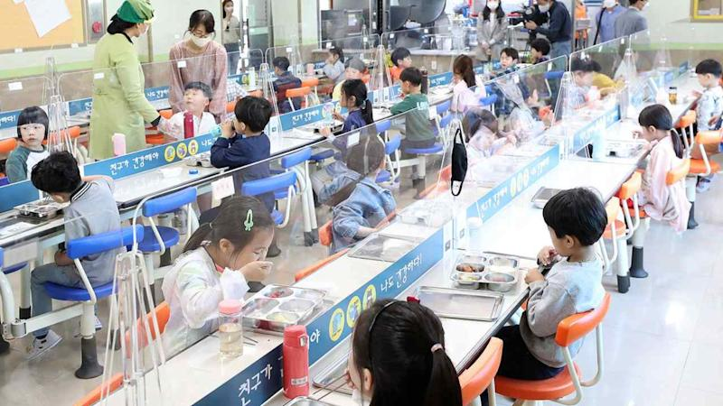 Students having lunch with transparent dividers separating them at the canteen of an elementary school in South Korea, in May. Image: Twitter/Jeff Ballinger