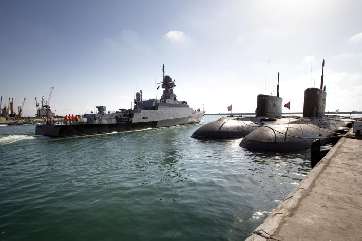 A Russian navy missile ship 'Veliky Ustyug' sails off from the Russian naval facility in Tartus, Syria, on patrol in eastern Mediterranean, Thursday, Sept. 26, 2019. Two Russian diesel-electric submarines of the project 636.3 Varshavyanka' are seen on the right. Russia has a naval base in Tartus, the only such facility it has outside the former Soviet Union. (AP Photo/Alexander Zemlianichenko)