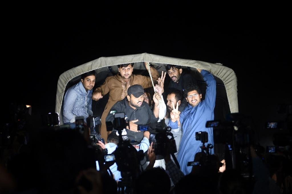 Activists from the Pakistan Tehreek Insaaf party shout slogans from inside a police van after being arrested in Islamabad on October 27, 2016 (AFP Photo/Farooq Naeem)