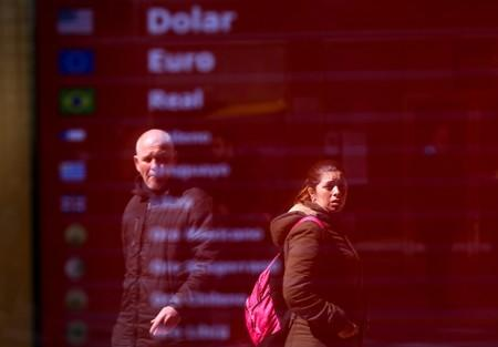 People are reflected in an electronic board that shows currency exchange, in Buenos Aires