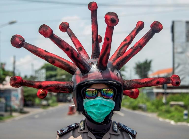 Indonesian police officers spread the message with special helmets while disinfecting vehicles