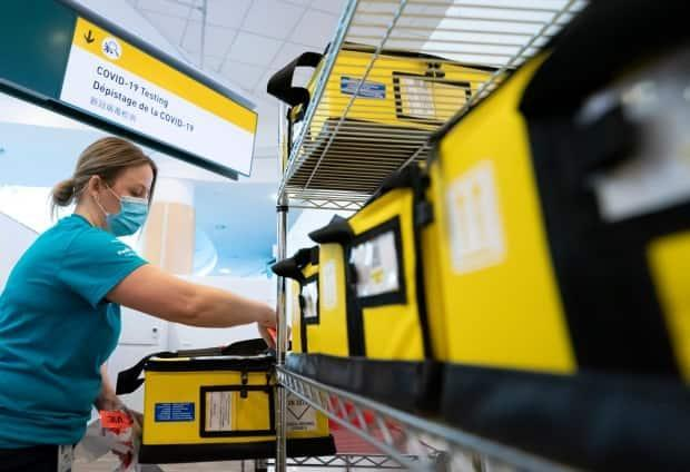 A LifeLabs employee helps set up a COVID-19 screening centre at Vancouver International Airport on Feb. 19. The auditor general says the Public Health Agency of Canada was caught flat-footed by the pandemic and initially underestimated the threat. (Jonathan Hayward/The Canadian Press - image credit)
