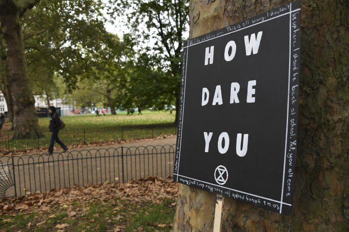 A banner leans up against a tree in London, Monday, Oct. 7, 2019. (Photo: Alberto Pezzali/AP)