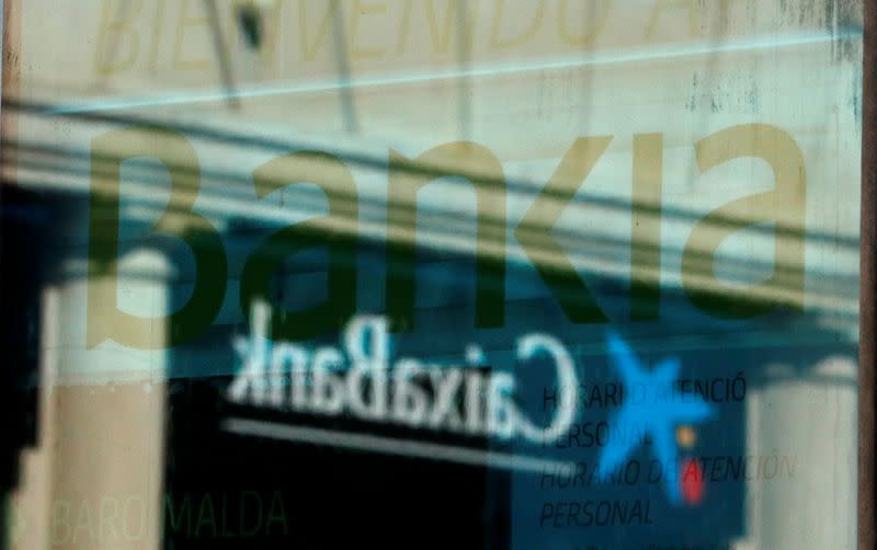 Logos of Caixabank and Bankia are seen at bank offices near Barcelona