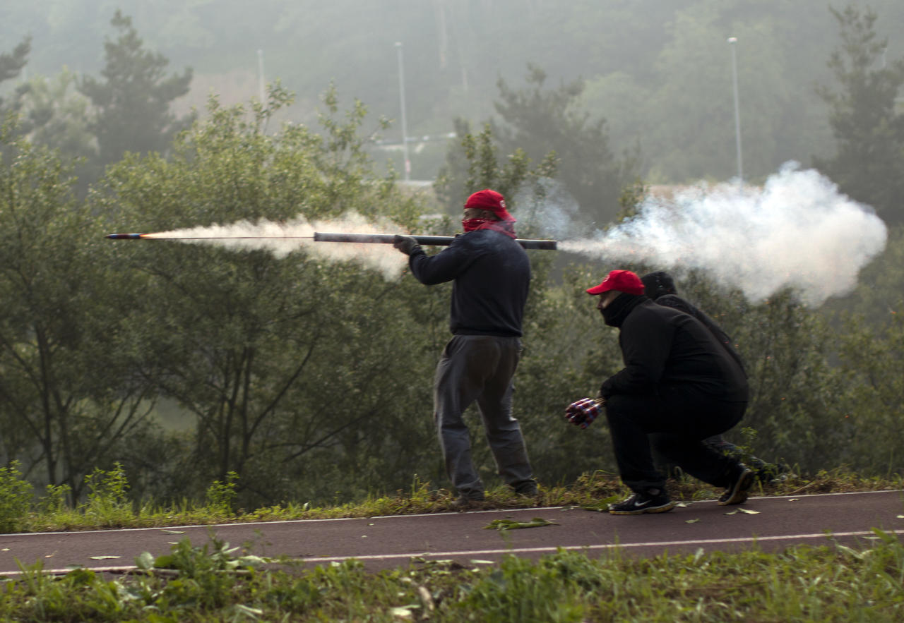"""Miners fire handmade rockets at riot police officers, unseen, as they defend their positions near the mine """"El Soton"""" during clashes in El Entrego near Oviedo, Spain, Friday, June 15, 2012. Strikes, road blockades, and mine sit-ins continue as 8,000 mineworkers at over 40 coal mines in northern Spain continue their protests against government action to cut coal subsidies. (AP Photo/Emilio Morenatti)"""