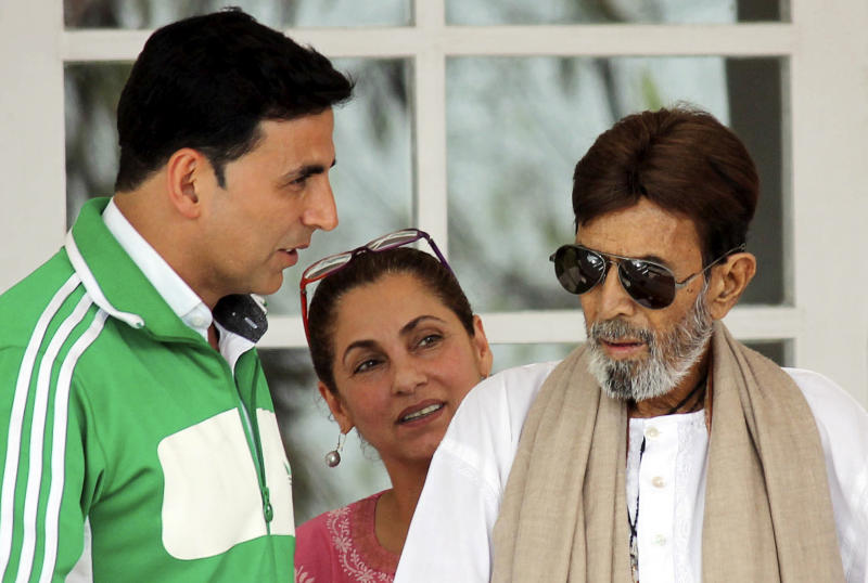 In this photo taken June 20, 2012, Indian Bollywood star Rajesh Khanna, right, speaks with son-in-law and Bollywood actor Akshay Kumar, left, as his wife actress Dimple Kapadia looks on in Mumbai, India. Khanna, the first Hindi film actor to gain superstar status in Indian films, died Wednesday, July 18, 2012 after a brief illness. He was 69. (AP Photo)
