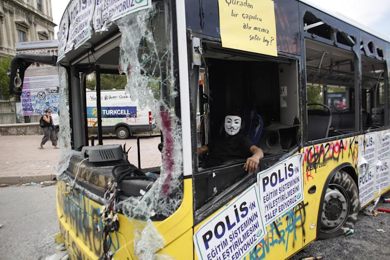 """A protester sits in a damaged bus at Taksim square of Istanbul, Thursday, June 6, 2013. The placards read """"We demand the improvement of the education system in the police"""" . The Turkish officials, scrambling to contain tensions, have delivered more conciliatory messages to thousands of protesters denouncing what they say is the government's increasingly authoritarian rule and its meddling in lifestyles. (AP Photo/Kostas Tsironis)"""