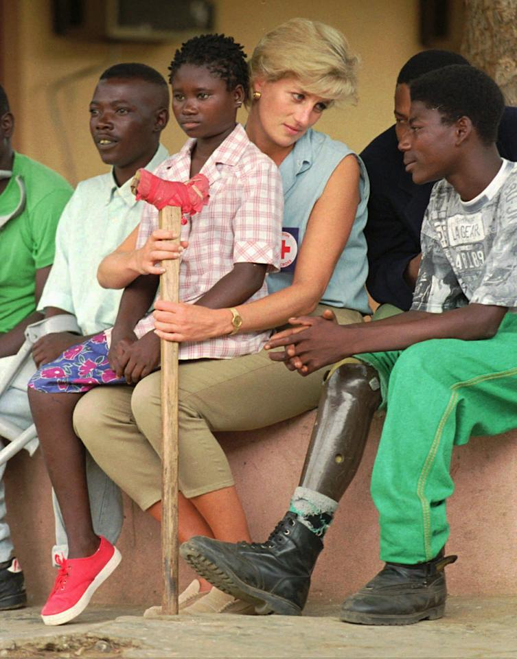 FILE - In this Jan. 14, 1997 file photo, Britain's Princess Diana talks to amputees at the the Neves Bendinha Orthopedic Workshop on the outskirts of Luanda, Angola. Sitting on Diana's lap is 13-year-old Sandra Thijica, who lost her left leg to a land mine while working the land with her mother in Saurimo, eastern Angola, in 1994. Princess Diana would have been 50 years old on Friday, July 1, 2011, perhaps the only certainty about the course of a life abruptly cut short in a 1997 car crash in Paris, with a new boyfriend, two months past her 36th birthday. (AP Photo/Joao Silva, file)