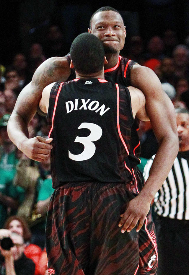 Cincinnati's Yancy Gates (34) hugs Dion Dixon (3) during the second half of an NCAA college basketball game against Syracuse in the semifinals of the Big East Conference tournament in New York, Friday, March 9, 2012. Cincinnati won 71-68. (AP Photo/Frank Franklin II)