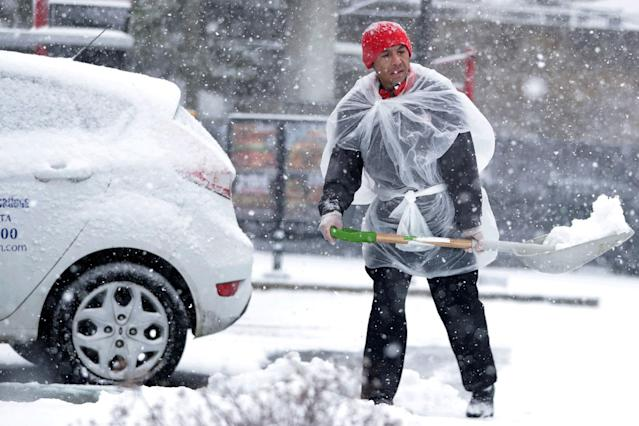 <p>A restaurant employee uses a large bag for protection while shoveling snow off the parking lot during a snowstorm, Wednesday, March 21, 2018, in Jersey City, N.J. (Photo: Julio Cortez/AP) </p>
