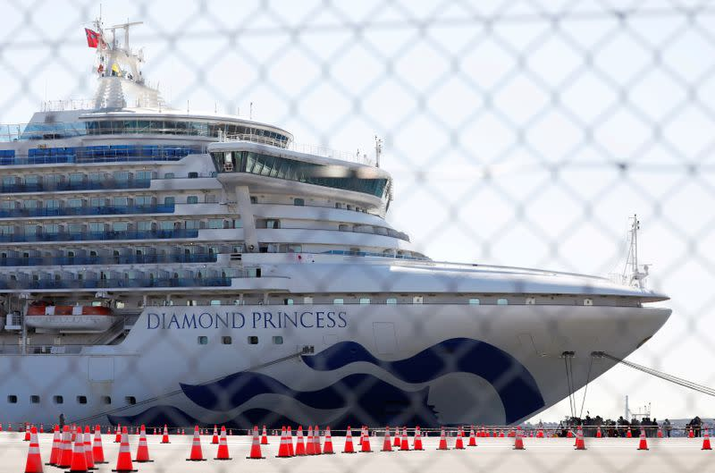 FILE PHOTO: The Diamond Princess, where many passengers have tested positive for coronavirus, is seen through steel fence at Daikoku Pier Cruise Terminal in Yokohama